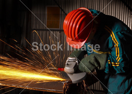 Heavy industry manual worker with grinde